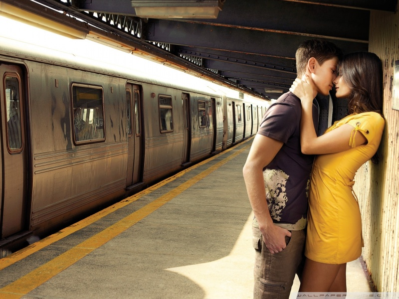 attractive couple kissing in the subway