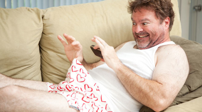 Middle aged man sexting from couch