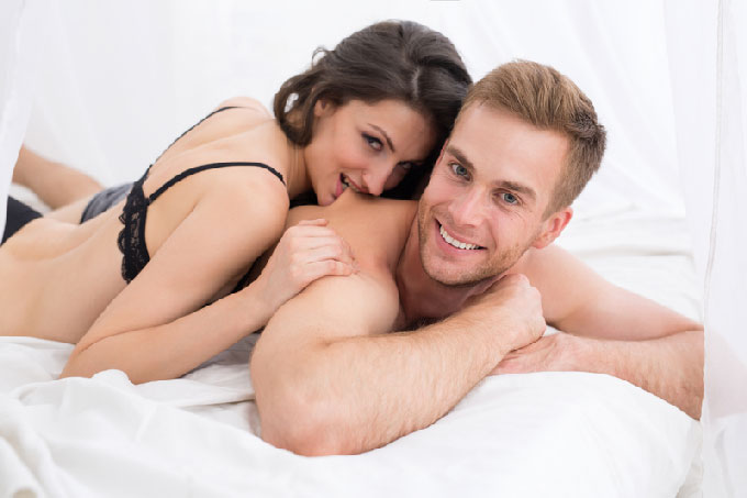 Radiant couple in bed after sexual intercourse